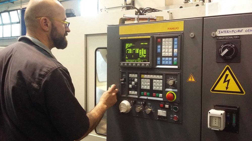 operaio che lavora su una macchina a controllo numerico