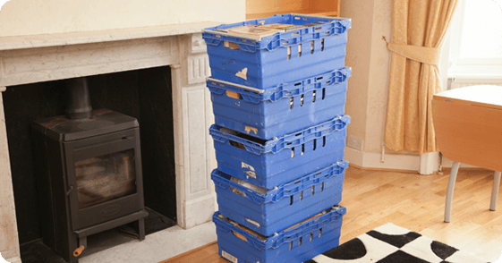 Stacks of plastic crates in front of a bare bookcase