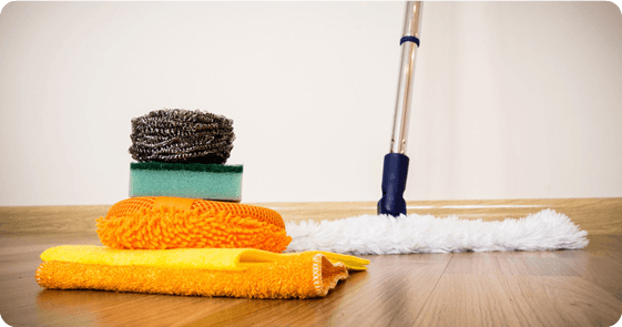 A mop and other cleaning tools on a wooden floor
