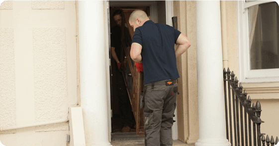 All Clear workers moving a cabinet out of a tight space