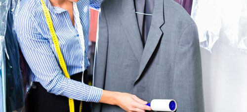 Women lint cleaning on suit in Canandaigua