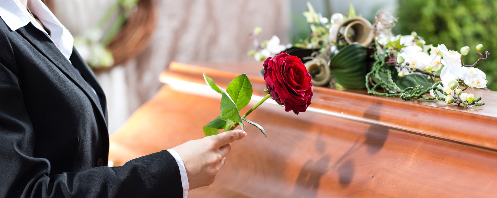Man holding red rose over the coffin