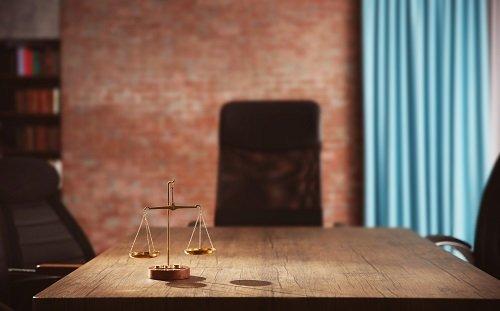 una bilancia giudiziaria su un tavolo di legno
