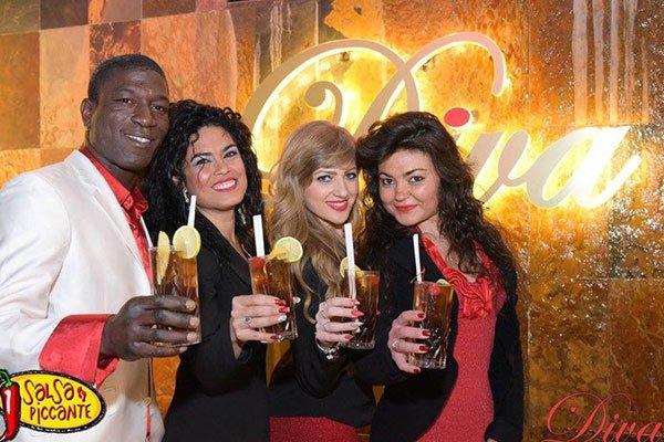 un ragazzo e tre ragazze in posa con dei cocktail in mano