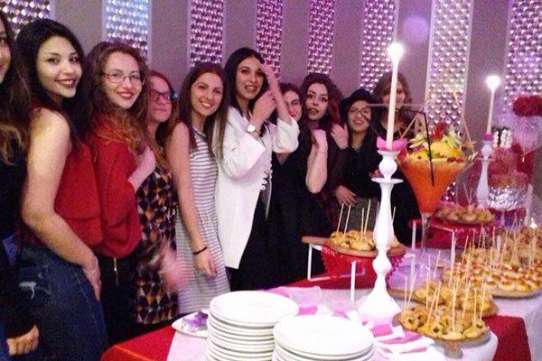 delle ragazze davanti un buffet con degli antipasti e un bicchiere di cocktail gigante