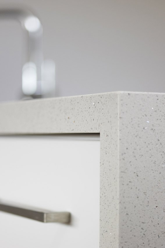 Closer view of the white with black dots quartz surface installed on the storage cabinets