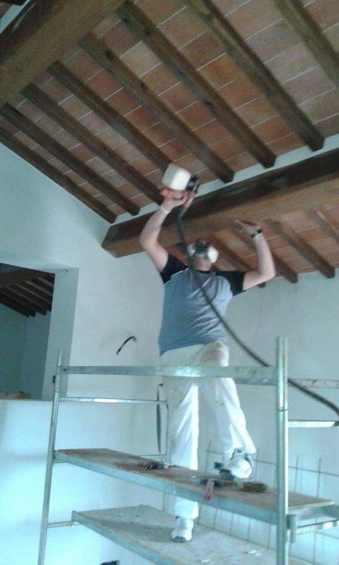 operaio mentre sistema delle travi a vista su un soffitto