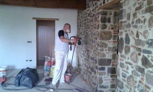 operaio mentre lavora su una parete in pietra
