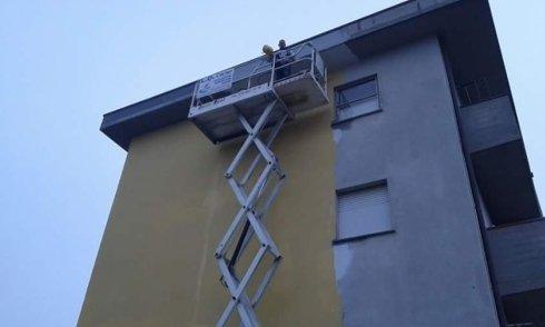 operai su un cestello elevatore tinteggiano la parete di un edificio