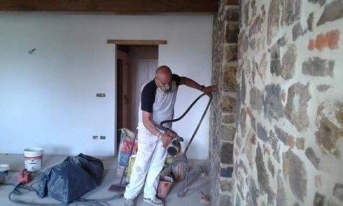 operaio che lavora una parete in pietra