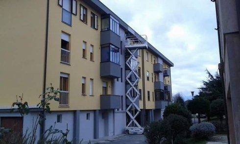vista laterale di un condominio e cestello elevatore