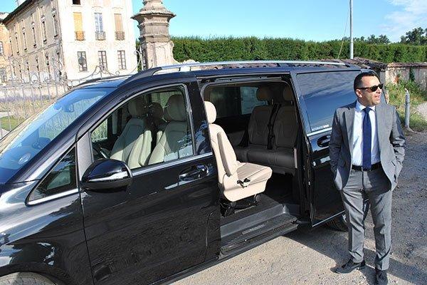 Vista laterale di minivan con portiera aperta e autista