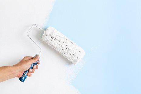 primo piano di mano del pittore in guanto bianco dipingere una parete con rullo di vernice