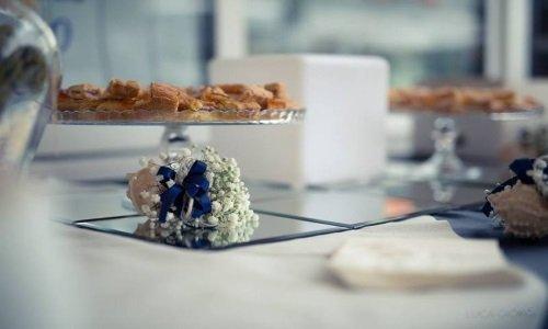 un piccolo bouquet di fiori bianchi con un nastro blu e sopra un porta torta con dei biscotti