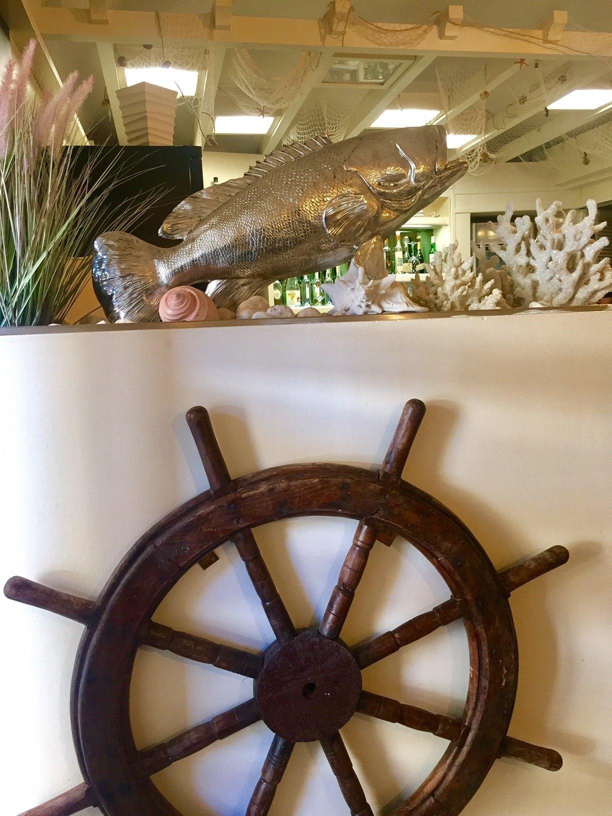 un timone di legno e sopra una statuetta di un pesce