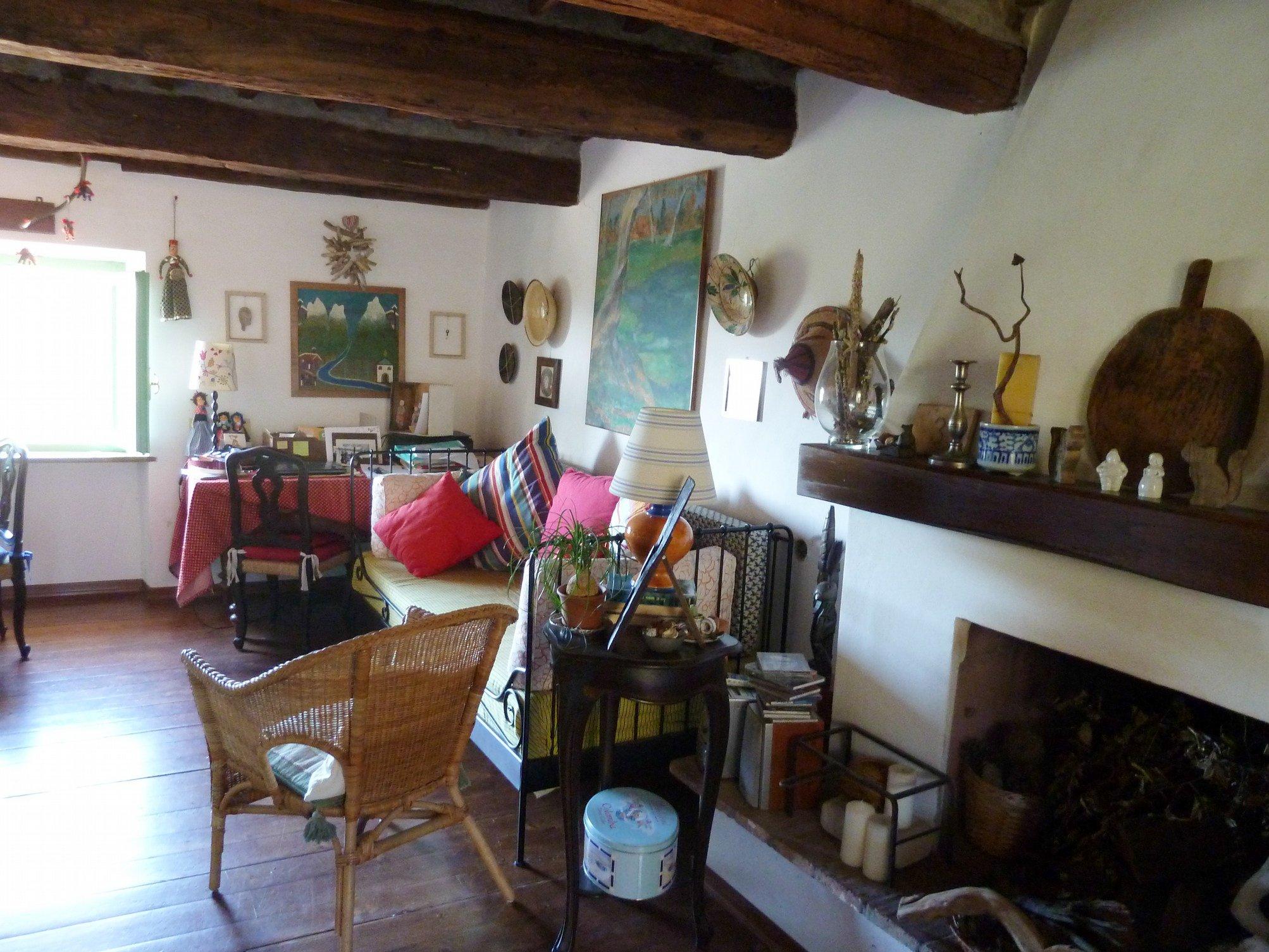 Una stanza con un tetto in legno, un divano in metallo con dei cuscini colorati e una poltrona in paglia
