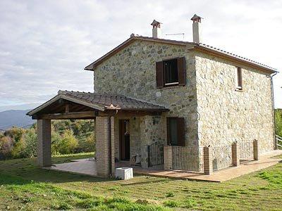 una casa in pietra e vista delle colline