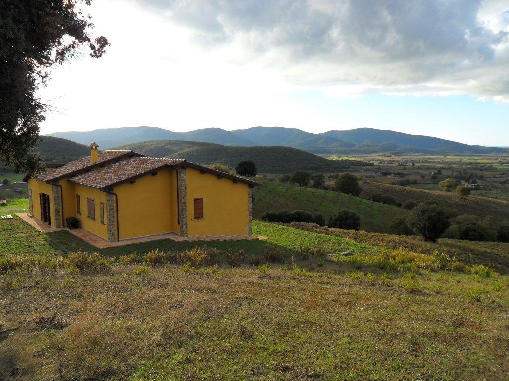 Una villa di color giallo e vista delle colline