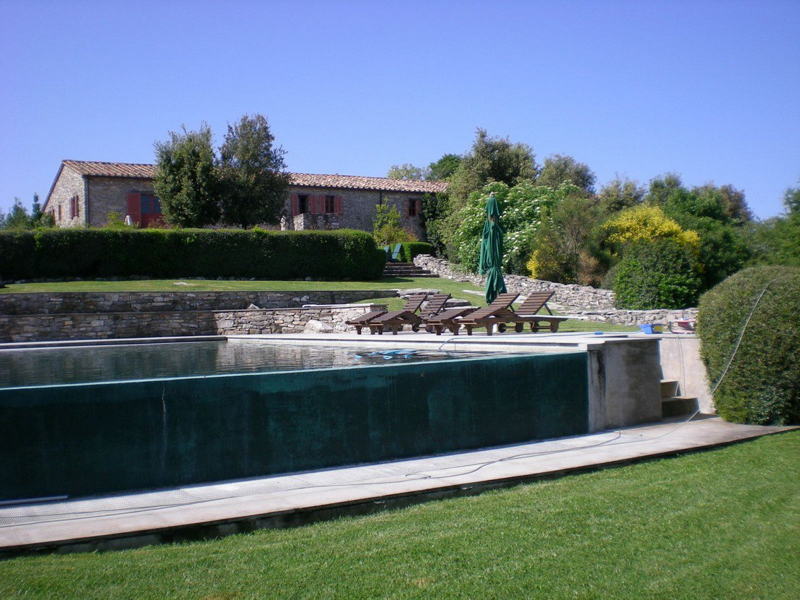 Una piscina davanti a una villa con alcuni sdraio
