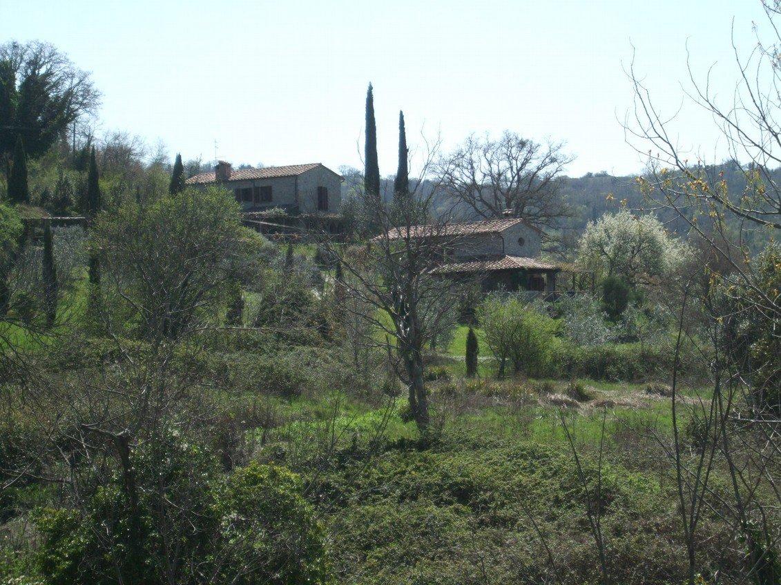 vista da lontano di una casa in pietra e dei cipressi