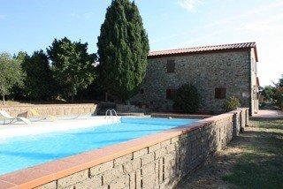 Una piscina accanto a una casa in pietra