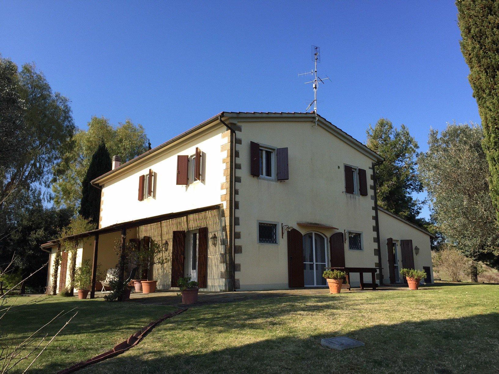 Una villa di due piani di color beige vista dall'esterno