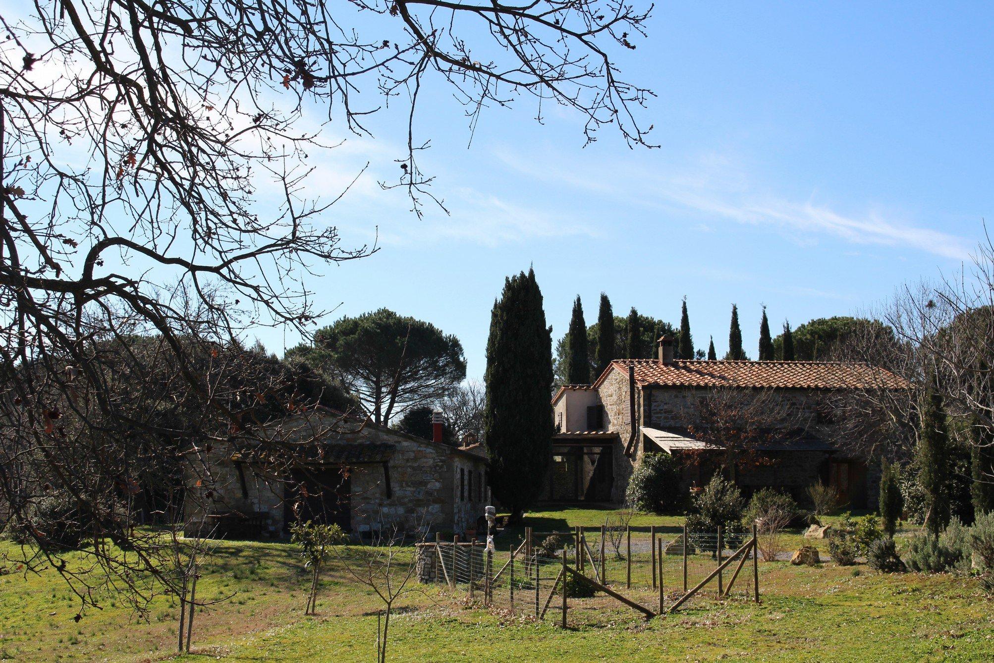 Due case in pietra e dei cipressi intorno