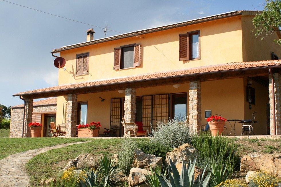 Un casa a  due piani e dei vasi di fiori rossi davanti