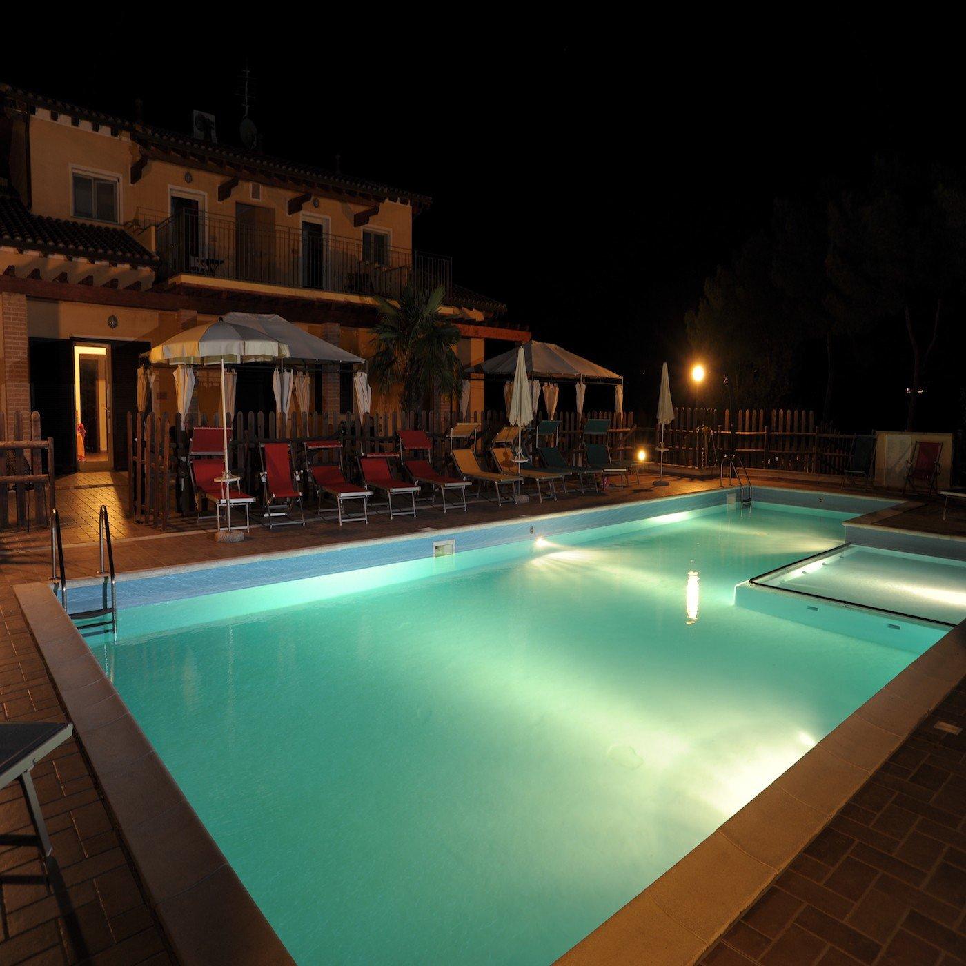 Una villa di due piani con una piscina con luci accese