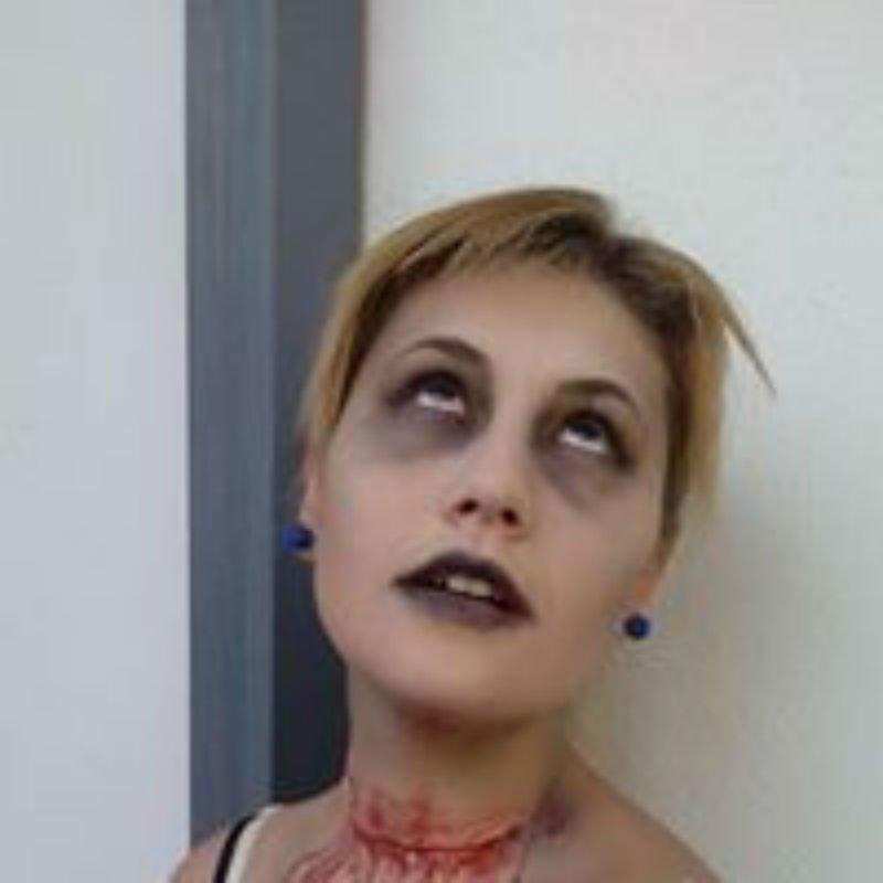 il viso di una donna con un ombretto di color nero e sul collo un trucco di un taglio e del sangue