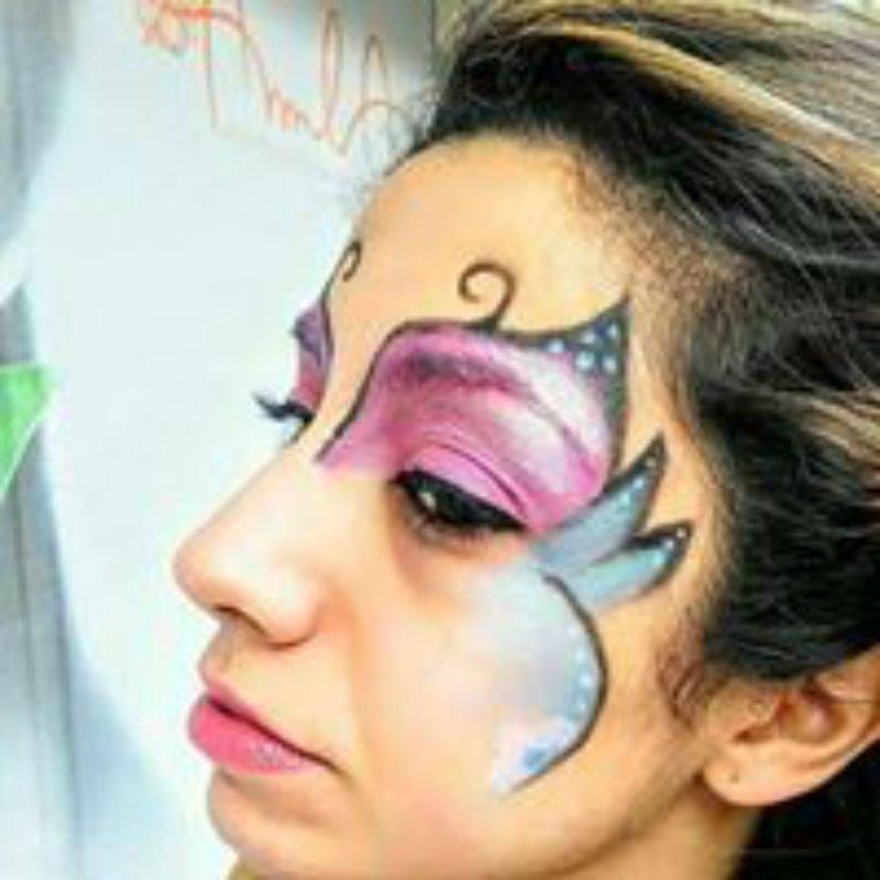 una donna con una pittura facciale di color viola e azzurro