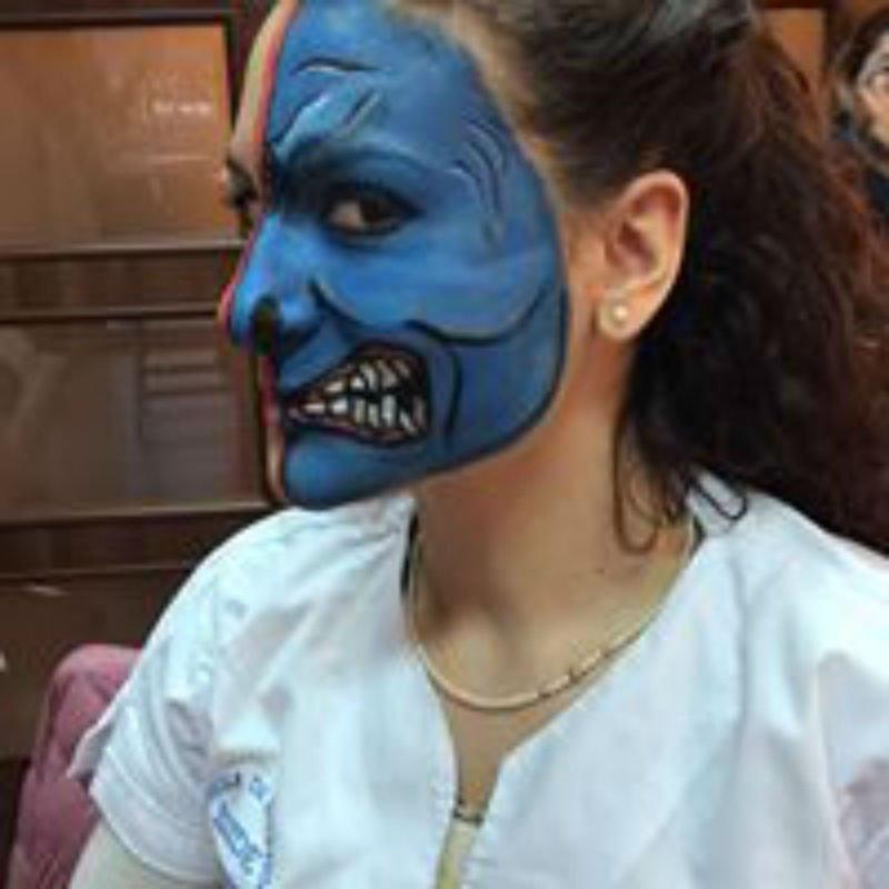 una ragazza con una pittura facciale di un mostro di blu