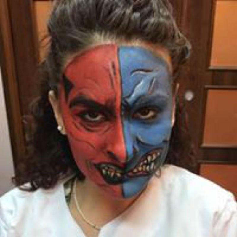 una donna con una pittura facciale di un mostro di color rosso e blu