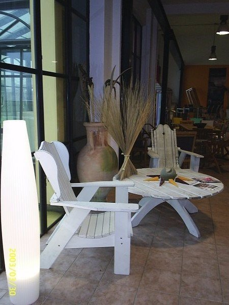 una sedia bianca, un tavolo e un vaso