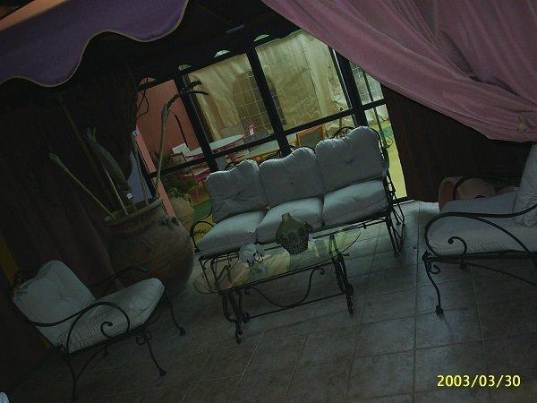 un divanetto bianco, un tavolino e due poltrone da esterno in ferro battuto