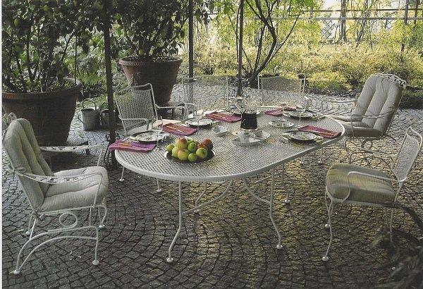 un tavolo in ferro battuto e delle sedie da esterno imbottite