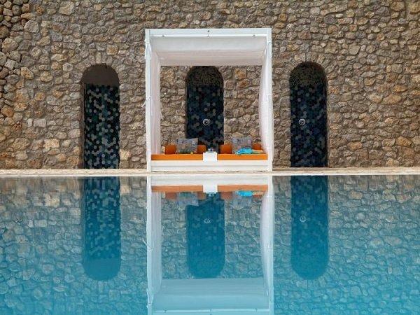 una piscina con vista di due divanetti sotto a una copertura