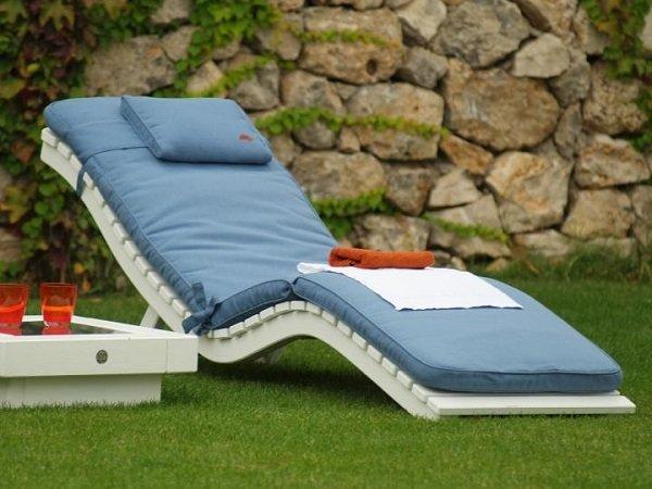 sdraio con cuscini blu in un giardino