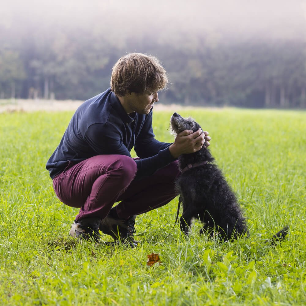 a man with his dog on a field