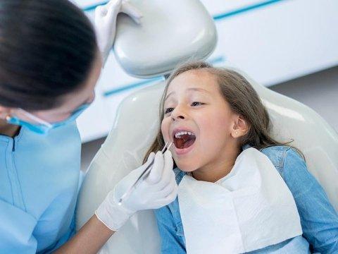 dentista mentre controlla denti di una bambina