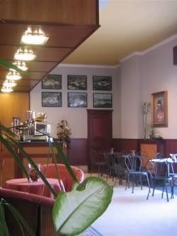 un bar con davanti dei tavoli e delle sedie