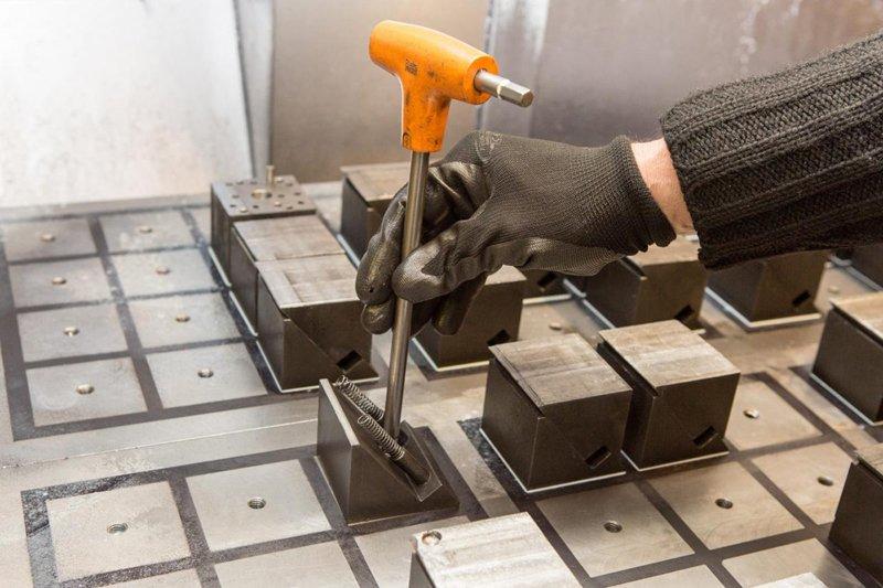 Un operaio con guanto effettua una trivellazione di precisione di una lastra