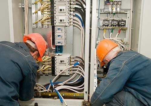 Due elettricisti che lavorano su un pannello industriale e montano nuovi cablaggi
