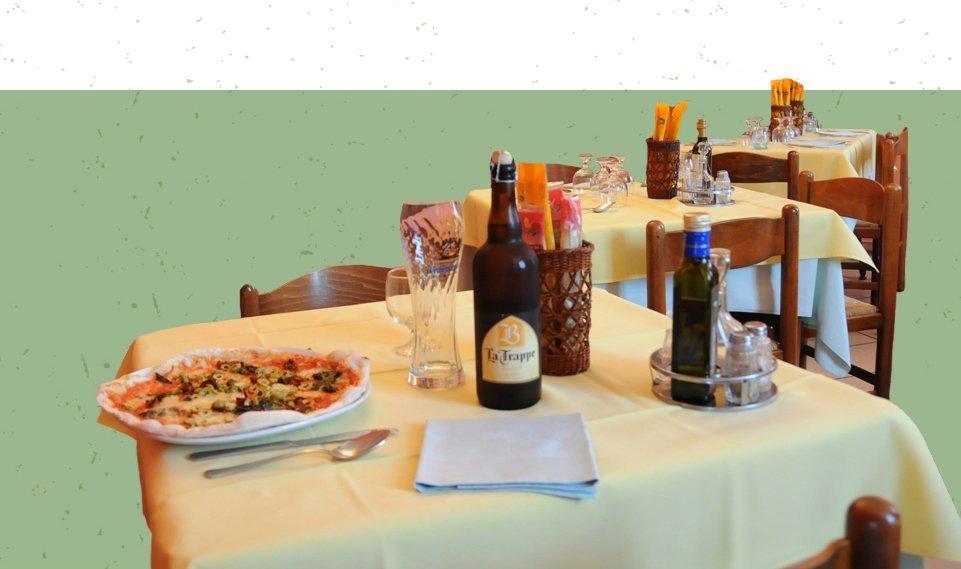tavolo apparecchiato con pizza e birra