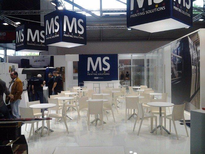 delle sedie, dei tavoli di color bianco e cartelloni con scritto MS printing solutions