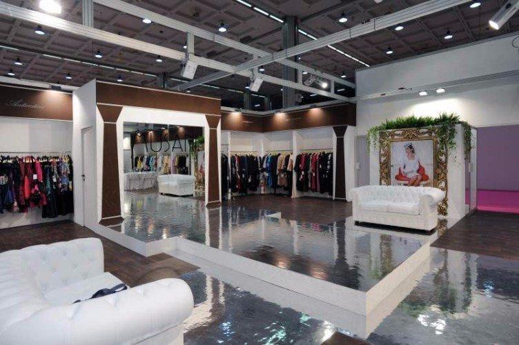 uno stand ampio di abbigliamento e due divani di pelle di color bianco