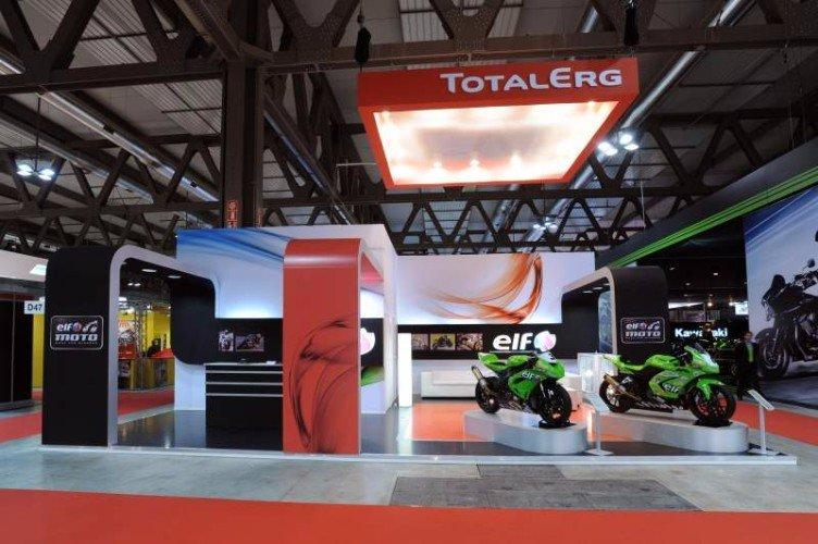 uno stand di Total Erg e accanto due moto della marca Kawasaki
