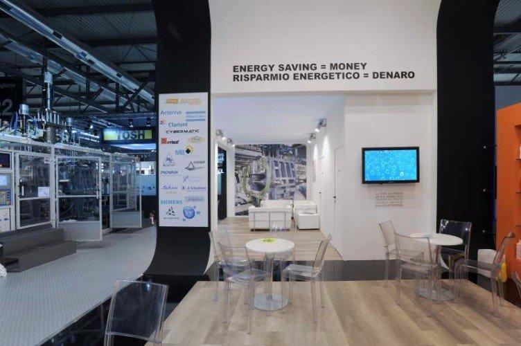 uno stand con un monitor al muro, accanto un pavimento in legno e dei tavoli
