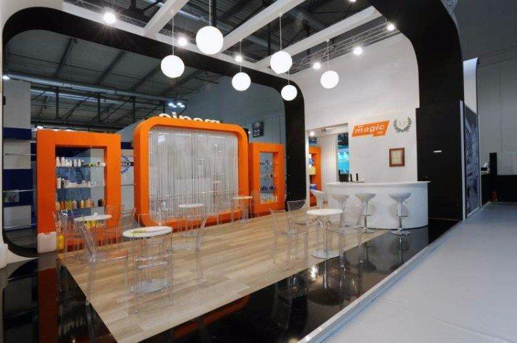 lo stand di Magic con un pavimento in legno e dei tavoli in plexiglass
