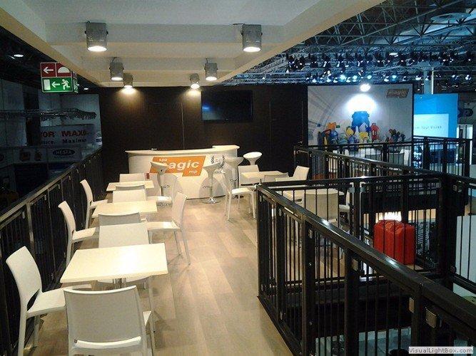 primo piano di uno stand con pavimento in parquet e di tavoli e delle sedie